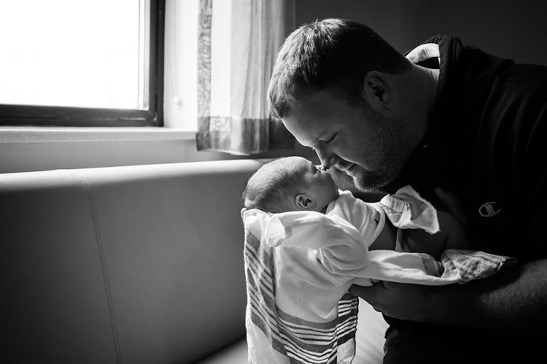 Father touching noses with newborn son in hospital