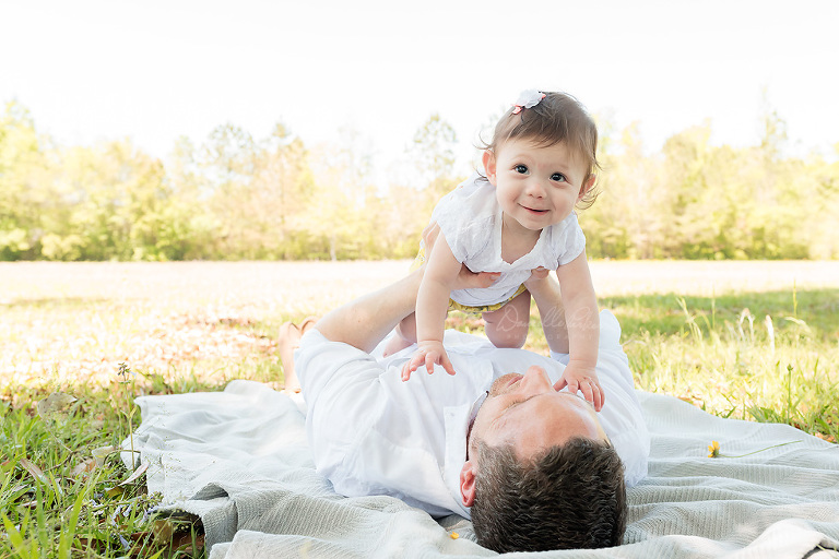 Father holding up baby daughter | Gulf Coast Mileston Photographer | Danielle Parker Photography