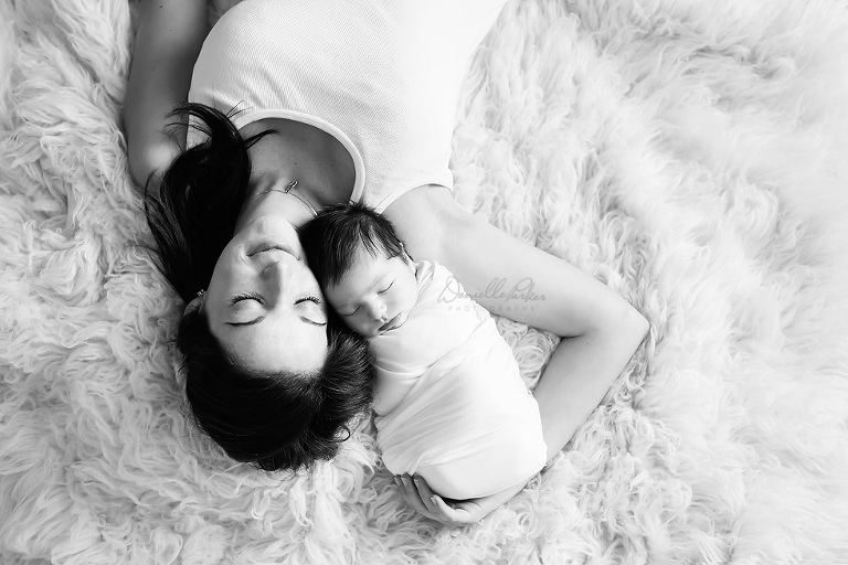 Black and White Picture of Mama with Newborn Son On Fur Rug | Mobile Newborn Photography | Danielle Parker Photography
