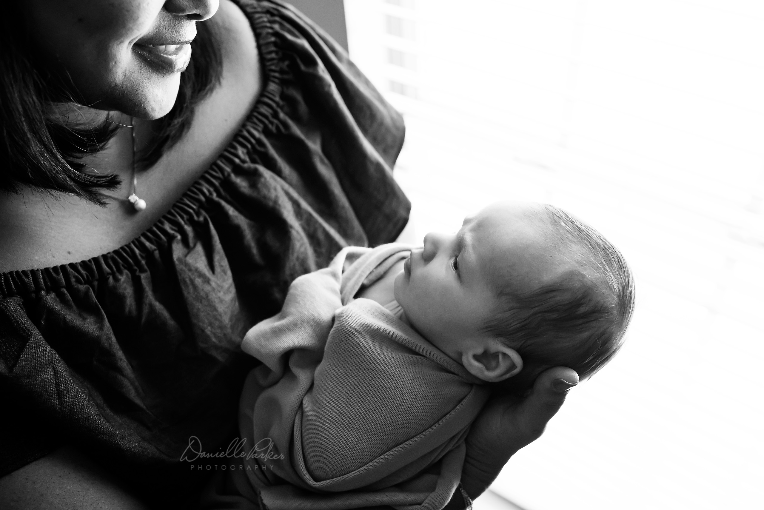 Black and White Photo of Mother Looking Down at Baby Son  | Lifestyle Newborn Photographer Mobile, AL | Danielle Parker Photography